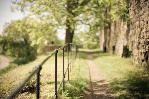 Обои Металлическая ограда вдоль тропинки, с другой стороны каменная стена