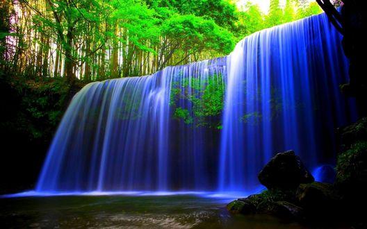 Обои Красивый водопад с голубым оттенком воды, падающий с небольшого горного плато в окружении деревьев с ярко-зеленой кроной