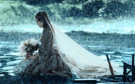 Обои Elizabeth Swann Turner / Элизабет Суонн Тлрнер в исполнении актрисы Keira Christina Knightley / Киры Кристины Найтли из серии фильмов Pirates of the Caribbean / Пираты Карибского моря в свадебном платье сидит в воде под ливневым дождем