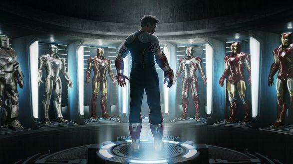 Обои Момент из фильма Iron man 3 / Железный человек 3, когда Тони Старк / Tony Stark, чью роль исполняет Роберт Дауни-младший / Robert John Downey, стоит перед своими костюмами