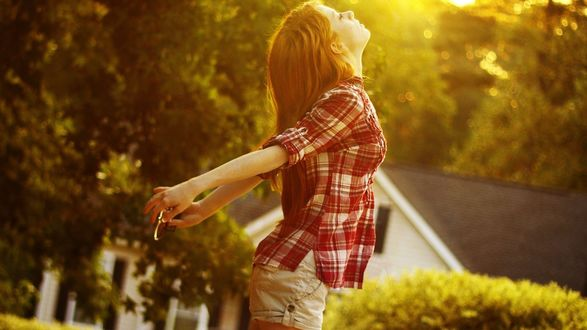 Обои Девушка в клетчатой рубашке закинула голову вверх, наслаждаясь солнечными лучами, на фоне дома и деревьев