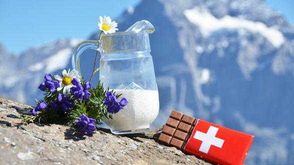 Обои На склоне горы лежит букет цветов, стоит кувшин с молоком и лежит плитка швейцарского шоколада