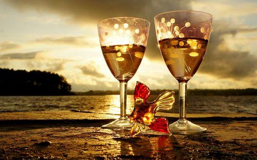 Обои Два бокала с шампанским стоят на берегу моря, рядом лежит стеклянная рыбка