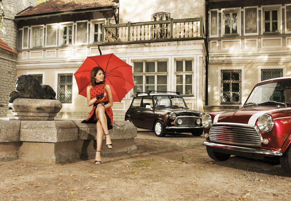 Обои для рабочего стола Девушка в красном платье в черный горошек, с красным зонтом сидит около статуи льва на фоне старинных автомобилей и жилого здания