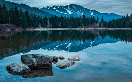 Обои В чистом горном озере видна гора, усыпанная снегом