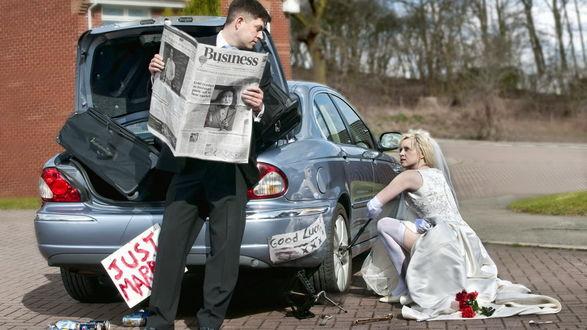 Обои Невеста в белом свадебном платье меняет пробитое колесо автомобиля, а жених невозмутимо читает газету, облокотившись на открытый багажник