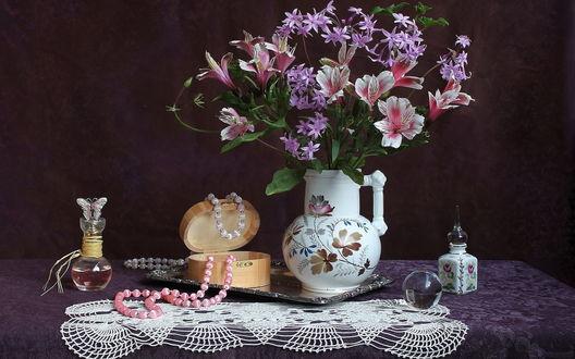Обои Цветы альстромерии, стоящие в красивом кувшине на столе с белой кружевной салфеткой, открытая коробочка с лежащими на ней бусами и флаконы с духами