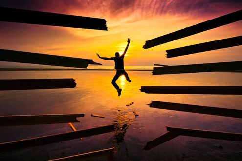 Обои Парень проломил деревянную преграду и с разбегу влетает в море на фоне закатного солнца