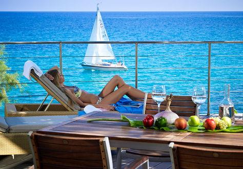 Обои Девушка отдыхает на шезлонге, в море проплывает яхта, а на столе расставлены вода, яблоки, виноград и сладкие перцы, курорт Villa Margarita, Халкидики, Греция / Halkidiki, Greece