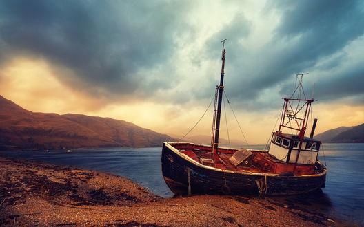 Обои Старый рыбацкий баркас, пришвартованный к песчаному берегу морской бухты. окруженной горами на фоне пасмурного неба