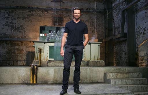 Обои Актер Hugh Jackman / Хью Джекман стоит в заводском помещении, позади какой-то агрегат