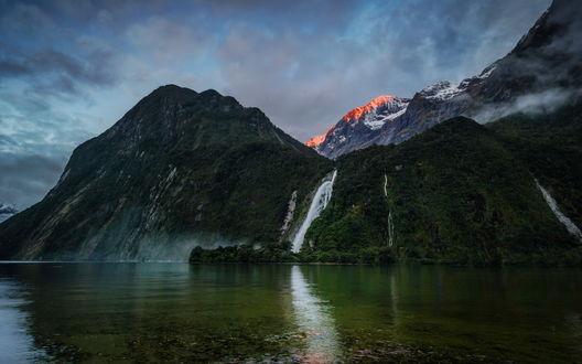 Обои Озеро с зеленоватым цветом воды, расположенное в горном массиве, покрытом густыми зелеными кустами и деревьями, водопадами на фоне пасмурного неба