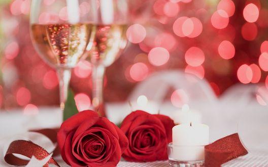 Обои Две красные розы лежат на столе рядом со свечой, на заднем плане стоят да бокала