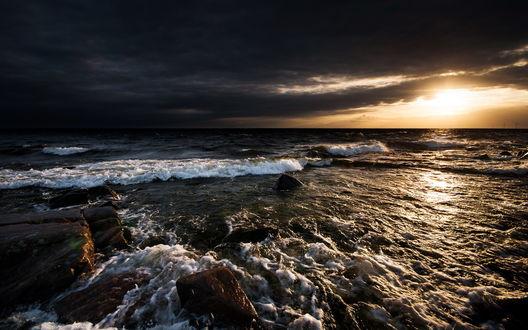 Обои Морские волны омывают каменистый берег на фоне пасмурного неба, вдалеке на берегу виднеются ветряки
