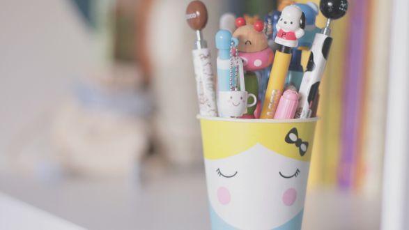 Обои Множество необычных ручек стоит в стаканчике с нарисованным лицом
