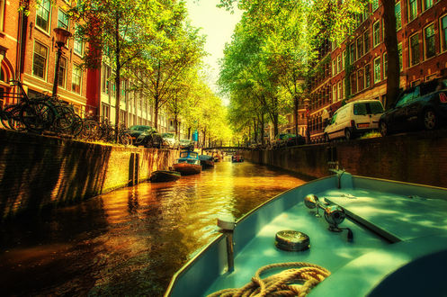 Обои Лодка плывет по каналу Амстердама / Amsterdam вдоль улицы с домами, машинами и велосипедами, Нидерланды / Netherlands
