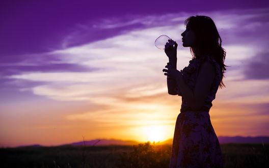 Обои Девушка выдувает большой мыльный пузырь на фоне фиолетового вечернего неба