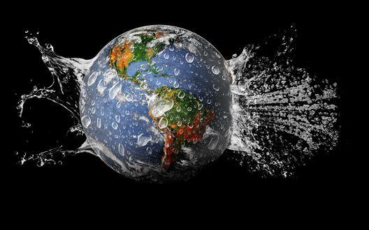 Обои Географический глобус планеты Земля, брошенный в емкость с водой, вызвал поток брызг и образования капель