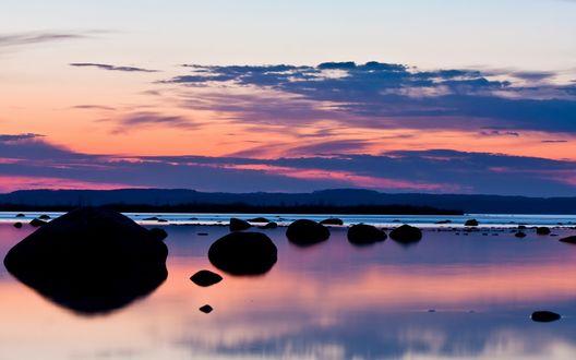 Обои Камни торчат из озера, в котором отражается вечернее небо на закате