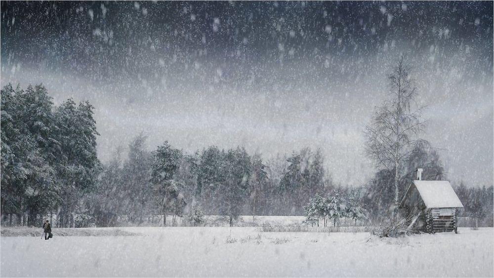 Обои для рабочего стола Человек идет к дому под сильным снегопадом