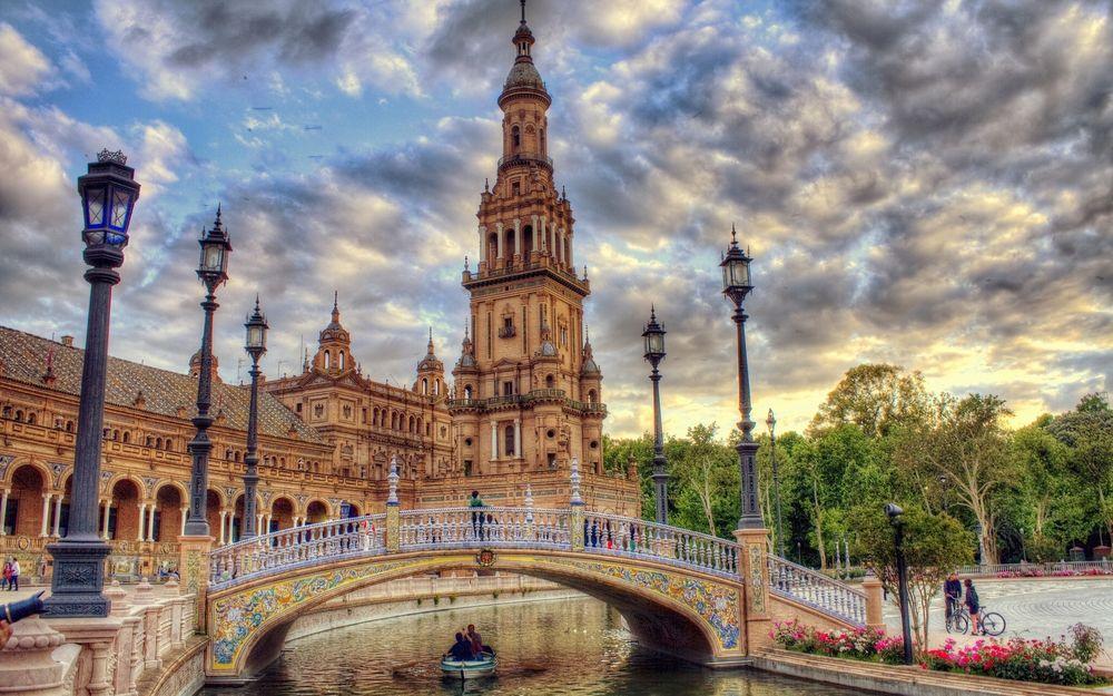 Обои для рабочего стола Площадь Испании / Plaza de Espana в Севилье / Seville с архитектурным выставочным комплексом, окруженный водоемом, через который пролегает мост и по бокам стоят фонари, фотограф Иисус Санчес / Jesus Sanches, Испания / Spain