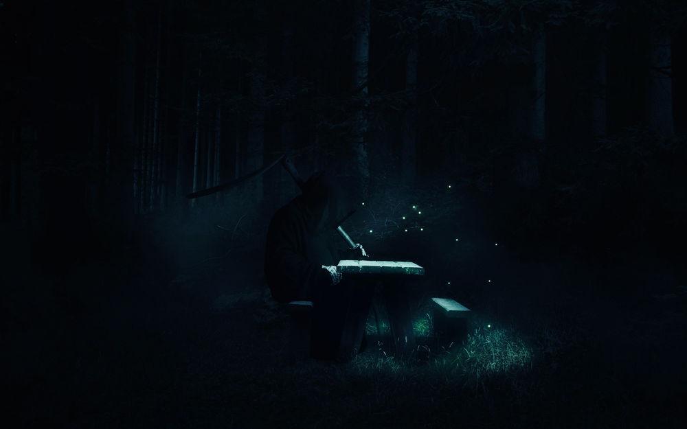 Обои для рабочего стола Смерть сидит за столом, над которым летают светлячки, в ночном лесу