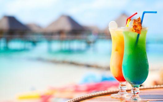 Обои Два коктейля на столе на фоне домиков в море