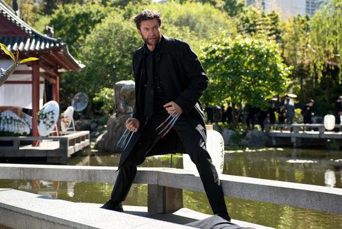 Обои Хью Майкл Джекман / Hugh Michael Jackman, кино герой Росомаха / Wolverine из фильма Люди Икс / X-men стоит на деревянном мосту у воды на фоне деревьев и дома с азиатской крышей Пагодой
