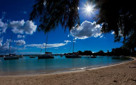 Обои Яркое полуденное солнце на голубом небе с белыми облаками осветило своими яркими лучами морскую песчаную бухту со стоящими у берега яхтами