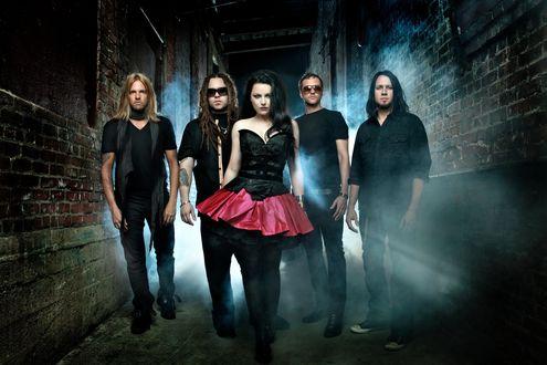 Обои Музыкальная группа Evanescence, солистка Amy Lee / Эми Ли, мужчины с девушкой стоят возле кирпичных стен домов, позади них темнота и туман