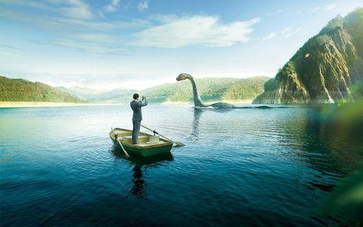Обои Мужчина, большой любитель сенсационных снимков, стоя в лодке, фотографирует Лох-Несское Чудовище / Loch Ness Monster, которое обитает на озере Лох-Несс, Шотландия / Lake Loch ness, Scotland