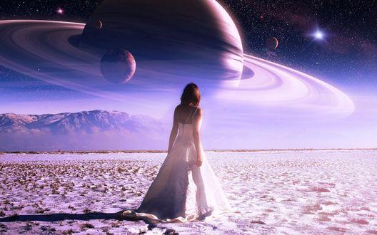 Обои Девушка в белом платье стоит на песке на фоне гор и неба, на котором видны планеты