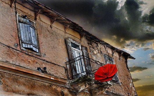 Обои Красный зонт висит на балконе старого дома
