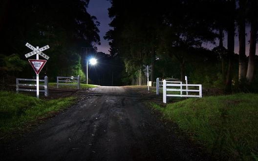 Обои Дорога, проходящая через железнодорожный переезд, на котором установлены предупреждающие знаки с надписями RAIL WAY GROSSING / Железнодорожное пересечение и GIVE WAY / Уступи дорогу, на фоне горящих уличных фонарей, деревьев и ночного неба