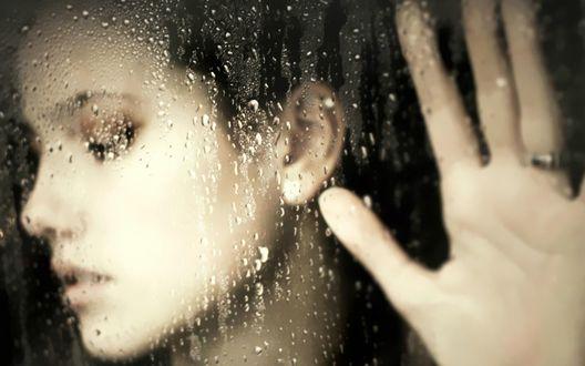 Обои Лицо девушки за окном, на стекле которого капли дождя