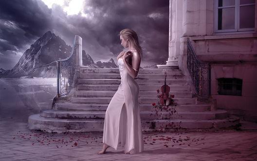 Обои Босоногая красивая белокурая девушка, одетая в длинное белое платье, ступает ногами по бетонному покрытию, усыпанному лепестками роз, на каменных ступеньках, ведущих в здание стоит виолончель, усыпанная алыми розами на фоне горного озера и пасмурного неба