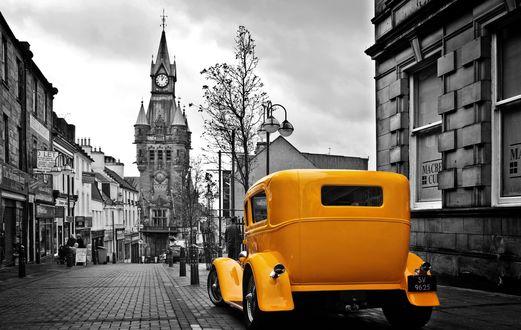 Обои Желтый автомобиль стоит на улице между домами, впереди видна башня с часами, растут деревья