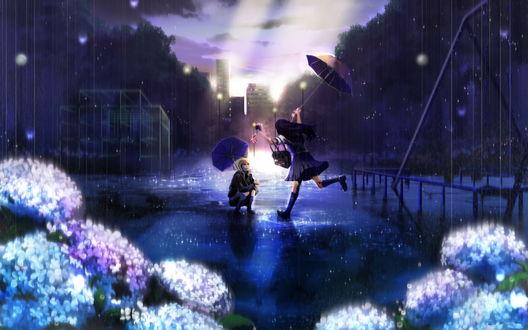 Обои Черноволосая девушка, держащая в одной руке зонтик, а в другой сумку и мобильный телефон, бегущая по лужам под дождем к другой, светловолосой девушке, присевшей под зонтом на дороге, проходящей между домами на фоне пробивающихся солнечных лучей заходящего за дома солнца; на переднем плане цветущая гортензия