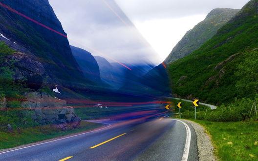 Обои Необычное явление в виде синей, прозрачной стены с красными полосками, возникшей над асфальтовой дорогой с указательным знаком Поворот налево, проходящей извилистой линией между горными массивами, поросшими деревьями и кустарником