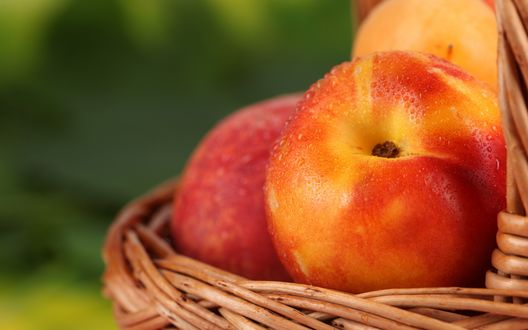 Обои Сочные и спелый персики в каплях воды лежат в плетенной корзине