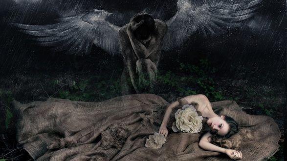 Обои Около девушки, лежащей на траве сидит мужчина-ангел, идет дождь