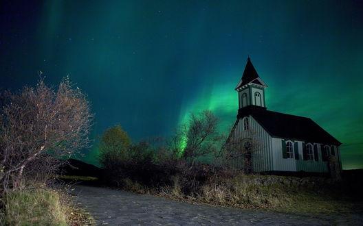 Обои Небольшая церковь стоящая на каменном фундаменте в окружении деревьев и проходящей мимо дороги на фоне ночного неба и красивого северного сияния