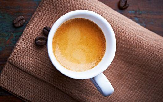 Обои Чашка кофе - эспрессо стоит на ткани, рядом рассыпаны зерна кофе, вид сверху