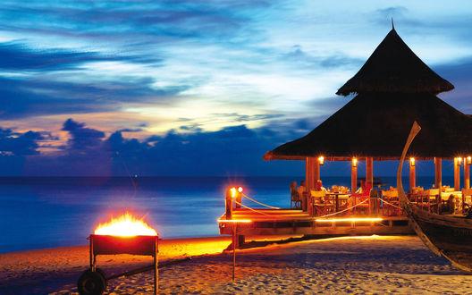 Обои Песчаный океанский берег с расположенной на нем верандой, покрытой тростниковой крышей, с сидящими за столиками с охлаждающими напитками и закусками отдыхающие люди, рядом стоит пылающий ярким пламенем мангал на фоне пасмурного вечернего неба, Мальдивы / Maldives