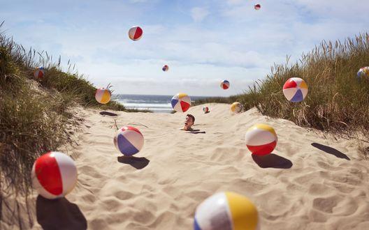 Обои Парень закопан по шею в песке по дороге на пляж, по которой скачут много разноцветных надувных мячей к морю