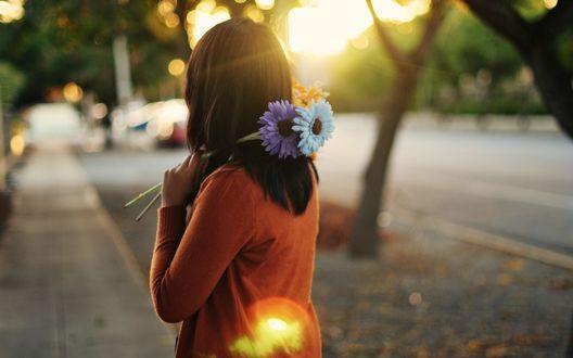 Обои Девушка с черными волосами в оранжевой кофте, держит в руках три цветка