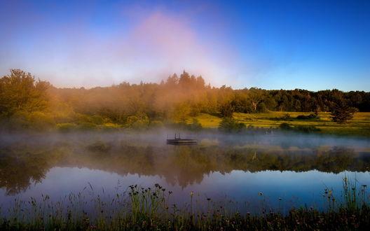 Обои Деревянный плот в реке, окруженной осенними деревьями, по которой стелется туман