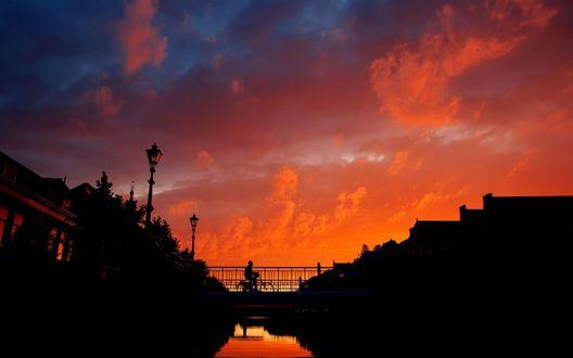 Обои Силуэт мужчины на велосипеде, едущего по мосту, проходящему через водный канал среди городских зданий на фоне вечернего заката