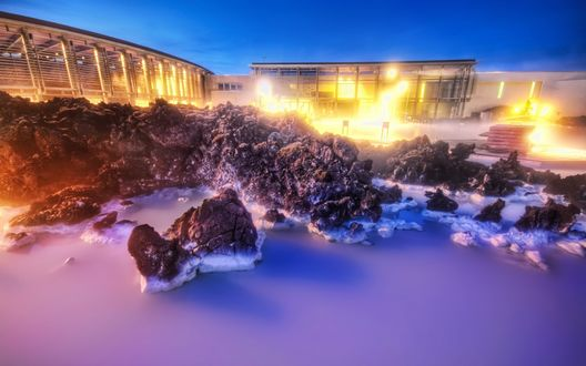 Обои Строящееся спортивное сооружение, освещенное ярким электрическим светом, расположенное возле каменных рифов морского побережья на фоне синего вечернего неба