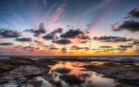 Обои Затопленный каменистый берег моря, над которым проплывают темные облака